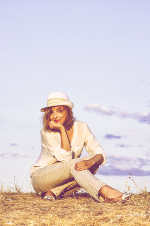 Pretty caucasian woman with stylish hat is sitting on dry grass by sunset with blue sky behind. Beauty and fashion. Seductive young woman. Washed film.
