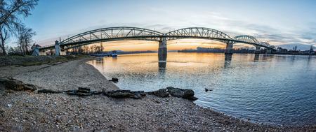 Maria Valeria bridge joins Esztergom in Hungary and Sturovo in Slovak republic across the Danube river. Transportation theme. Sunset scene. Stock Photo