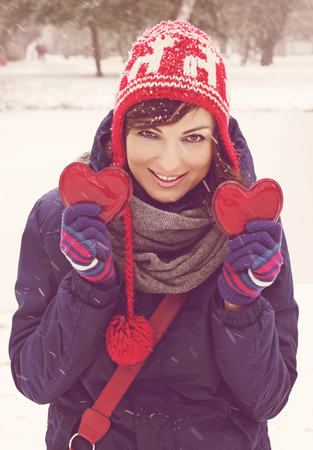 Young smiling woman with two red hearts in the winter park. Nostalgic filter. Valentines Day.