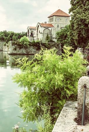 Beautiful castle in Tata, Hungary. Travel destination. Architectural theme. Beautiful place. Fortress, lake and greenery. Old photo filter.