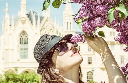 Young tourist woman sniffs flowering tree near Lednice castle, Moravia, Czech republic. Travel destination. Seasonal beauty. Yellow photo filter.