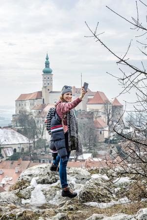 Joyful tourist woman is photographing with Mikulov castle, southern Moravia, Czech republic. Travel destination.