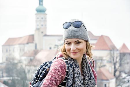 Joyful tourist woman posing with Mikulov castle, southern Moravia, Czech republic. Travel destination.