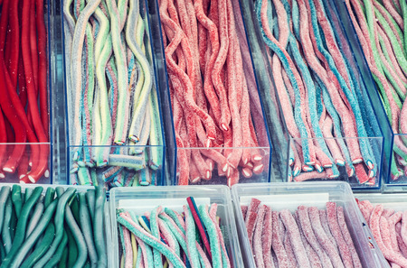 Multicolor tasty licorice candies in plastic containers. Sweet delight. Confectionery in the shop. Sweetmeats scene. Vibrant colors. Blue photo filter.