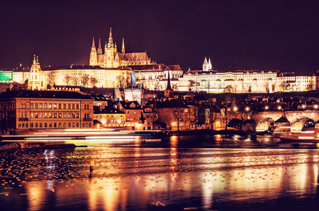 Famous castle and Charles bridge mirroring in Vltava river, Prague, Czech republic at night