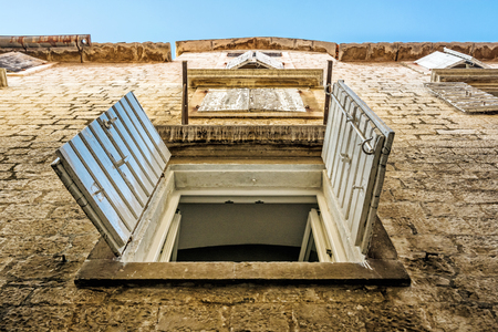 Windows with shutters on the old house, Trogir, Croatia. Travel destination. Architectural theme. Stock Photo