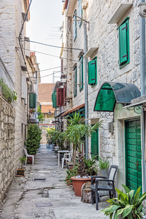 Narrow street in historic town Trogir, Croatia. Morning scene. Travel destination. chairs and plants.