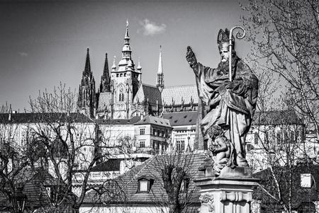 Saint Augustin statue, Charles Bridge and Prague castle. Religious architecture. Travel destination. Cultural heritage. Black and white photo.