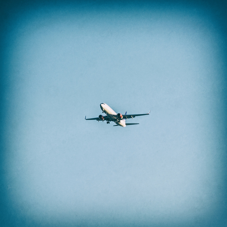 Aircraft is landing in the holiday destination. Summer vacation. Transporting theme. Analog photo filter with scratches. Stock fotó