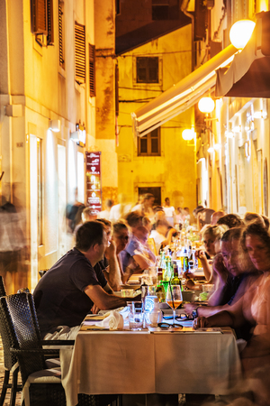 POREC, CROATIA – AUGUST 10, 2018: Tourists are sitting in the garden restaurant, old town of Porec, Croatia. Evening time in summer vacation destination. Illustrative editorial.