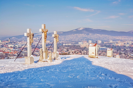 Calvary in Nitra city with Zobor hill, Slovak republic. Religious place. Winter scene. Cultural heritage. Travel destination. Snow and sunny. Purple photo filter. Stock Photo