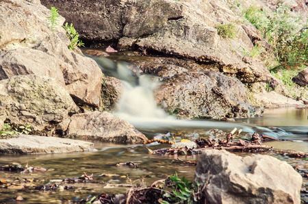 Water stream. Long time photo exposure. Detailed natural photo. Brook scene. Retro photo filter. Standard-Bild