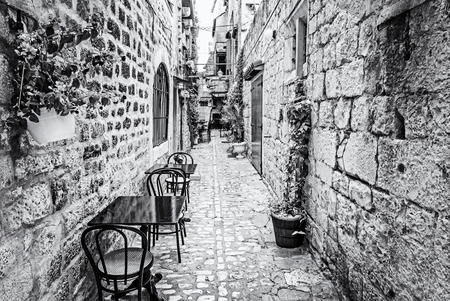 Narrow street in historic town Trogir, Croatia. Morning scene. Travel destination. Flowers, chairs and table. Black and white photo.