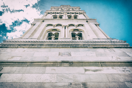 Cathedral of Saint Domnius in Split, Croatia. Religious architecture. Travel destination. Clouds and sun rays. Analog photo filter with scratches.