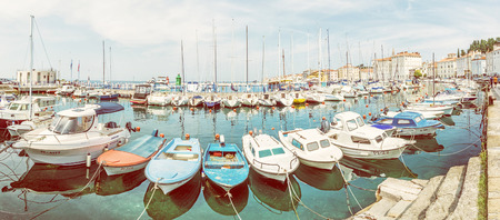 PIRAN, SLOVENIA – AUGUST 8, 2018: Many boats are mirrored in clean water, harbor in Piran, Slovenia. Panoramic photo. Summer vacation destination. Illustrative editorial. Yellow photo filter. Editorial