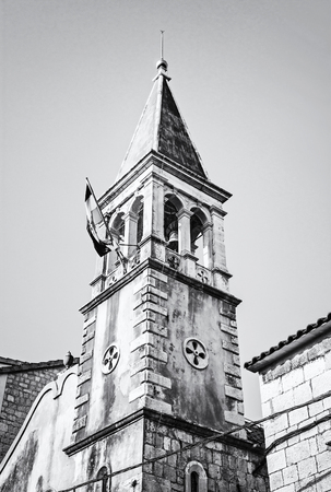 Church tower with Croatian flag in Trogir, Croatia. Religious architecture. Travel destination. Black and white photo.