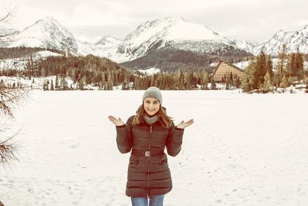 Smiling tourist woman posing in Strbske pleso resort, High Tatras, Slovak republic. Winter scene. Travel destination. Yellow photo filter.