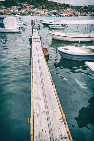 Wooden pier with boats in harbor, Trogir, Croatia. Travel destination. Sunset scene. Vertical composition. Analog photo filter with scratches. Stock fotó