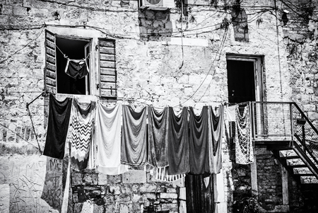 Drying clothes in front of the old house. Mediterranean architecture. Black and white photo.