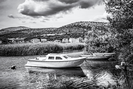 Boats with reflections in the beach bay, Pantan, Trogir, Croatia. Summer vacation destination. Black and white photo.