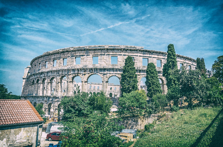 Ancient amphitheater located in Pula, Istria, Croatia. Travel destination. Famous object. Analog photo filter with scratches.