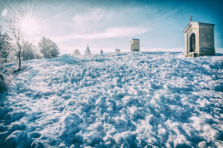 Calvary in Nitra city, Slovak republic. Religious place. Winter scene. Cultural heritage. Travel destination. Snow and sunny. Analog photo filter with scratches.