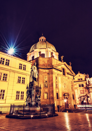 Charles IV statue and Church of Saint Francis of Assisi in Prague, Czech republic. Night scene. Religious architecture. Travel destination. Red photo filter.