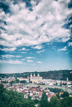 Passau city with Saint Stephen's cathedral, Lower Bavaria, Germany. Travel destination. Cultural heritage. Cloudy sky. Analog photo filter with scratches.