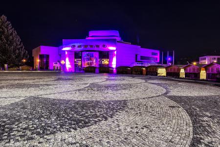 NITRA, SLOVAK REPUBLIC – NOVEMBER 17, 2018: Illuminated Andrej Bagar Theatre, wooden stands and Christmas tree on the square, Nitra, Slovak republic. Illustrative editorial. Cultural heritage. Night scene. Redakční