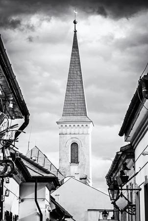 Hrnciarska street with Calvinist church in Kosice, Slovak republic. Folk art theme. Religious architecture. Black and white photo.