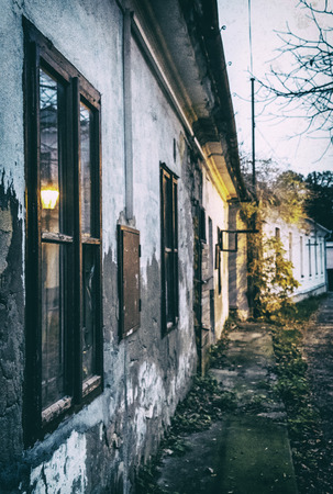 Old abandoned house in the evening light, Nitra, Slovak republic. Analog photo filter with scratches.