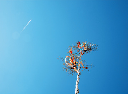 Looking up at may pole and aircraft on blue sky. European traditions. Teal and orange photo filter.
