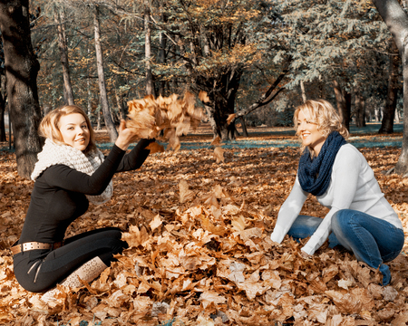 Two young caucasian women throwing yellow leaves in the autumn park. Teal and orange photo filter. 스톡 콘텐츠