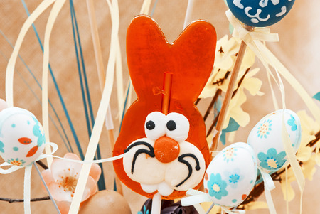 Lollipop-shaped Easter Bunny with painted eggs. Teal and orange photo filter.