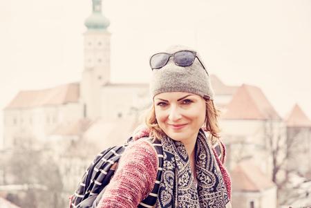 Joyful tourist woman posing with Mikulov castle, southern Moravia, Czech republic. Travel destination. Red photo filter.