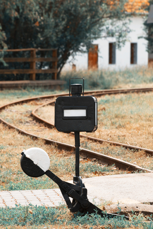Old railroad manual switch and railway. Teal and orange photo filter.
