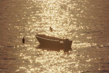 Swimmers and motor boat in backlight. Sunrise in Mediterranean Sea, Solta, Croatia. Summer vacation. Stock fotó