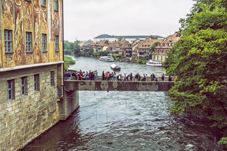 BAMBERG, GERMANY – JULY 12, 2019: Many tourists in artistic bridge and fishing district Little Venice in Bamberg, Bavaria, Germany. Travel destination. Architectural theme. Illustrative editorial.