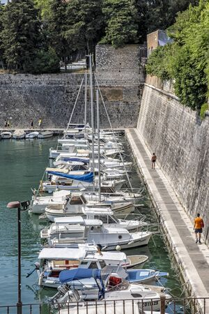 ZADAR, CROATIA – AUGUST 22, 2019: Many boats in the harbor and tourists, Zadar, Croatia, Europe. Summer vacation. Travel destination. Illustrative editorial.