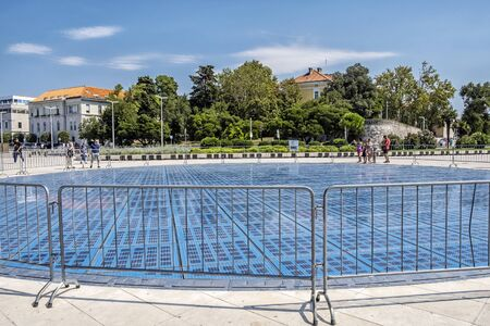 ZADAR, CROATIA – AUGUST 22, 2019: Sea organ is an architectural sound art object located in Zadar, Croatia and an experimental musical instrument, which plays music by way of sea waves and tubes located underneath a set of large marble steps. Illustrati
