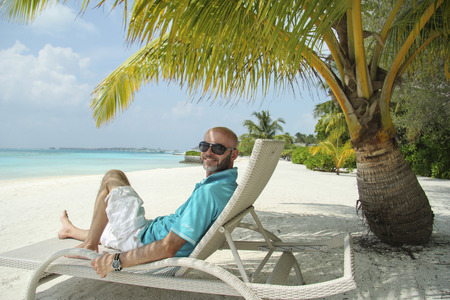 Man on a sun lounger under a palm tree in the Maldivian beach