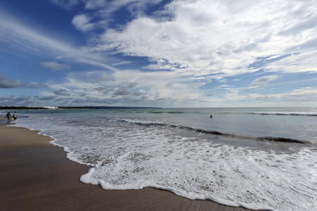 legian: Waves washing on shore of sandy Legian beach with turquoise ocean and clouds.