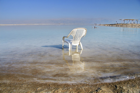 plastic chair in the water of the Dead Sea Stock Photo