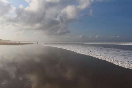Reflection of clouds on the shore of the ocean at low tide. Morning in Legian beach, Bali.
