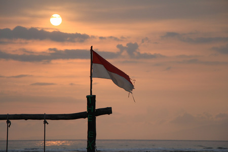 Indonesian flag on sunset and sea background