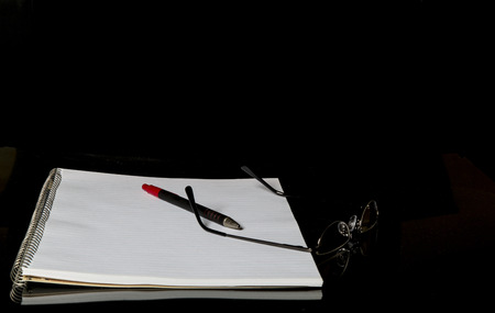 objects: Notebook and reading glasses with a red pen against a black background