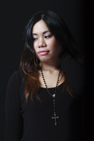 filipino adult: Pensive Filipino girl looking away on a dark background