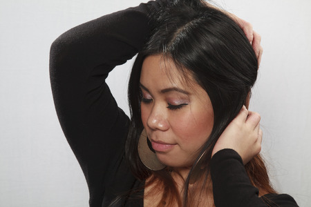 eyes closing: Pretty Asian girl stroking her hair and closing her eyes. Stock Photo