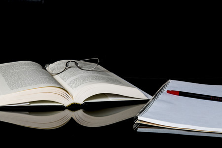 objects: Hardcover book notebook and reading glasses with a red pen against a black background