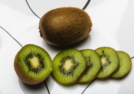 actinidia deliciosa: Sliced and Whole Kiwi Fruit on a white plate Stock Photo